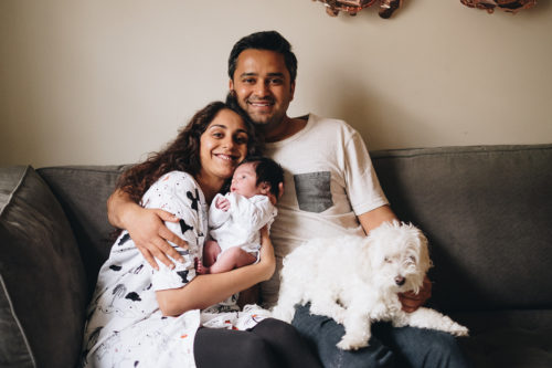 couple smiling with their newborn baby in london home